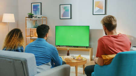 Diverse Group of Friends Sitting on a Couch at Home, Watch Green Chroma Key Screen TV while Eating Snacks and Drinking Beverage. Young People Having Fun at Home.