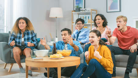 At Home Diverse Group of Sports Fans Sitting on a Couch Watching Important Sports Game Match on TV, They Cheer for the Team at a Very Tense Moment. Cozy Room with Snacks and Drinks. Banque d'images