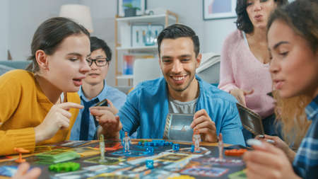 Diverse Group of Guys and Girls Playing in a Strategic Uniquely Designed Board Game with Cards and Dice. Friends Having Fun Reading Cards, Joking, Making Moves and Laughing in a Cozy Living Room Reklamní fotografie
