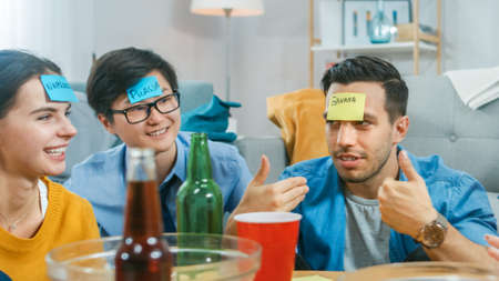 """In the Living Room Diverse Group of Fun Loving Friends Playing """"Who am I"""" game With Sticky Papers with Names on Written on them Attached to Foreheads. Guys and Girls Trying to Guess What is Written on"""