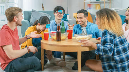 """In the Living Room Diverse Group of Fun Loving Friends Playing """"Who am I"""" game With Sticky Papers Attached to Foreheads. Guys and Girls Trying to Guess What is Written on Sticky Notes"""
