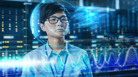 Young Asian IT Engineer Identified by Biometric Facial Recognition Scanning Process in Data Center Server Room. Futuristic Concept: Projector Identifies Individual by Illuminating Face by Lines.