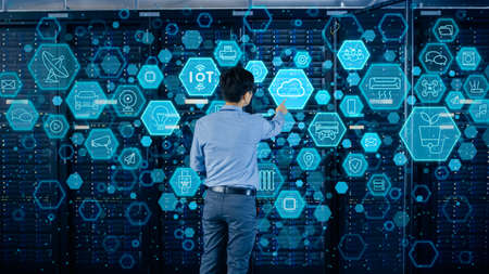 Concept of Cloud Data Storage. Shot In the Modern Data Center: IT Engineer Standing Beside Open Server Rack Cabinet and Touching Digital Illustrative Icons with Different Symbols and Visualisations.