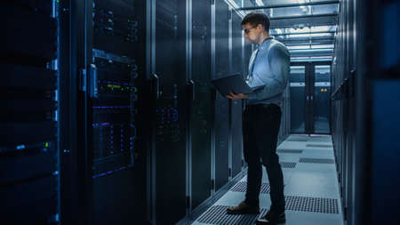 In Data Center IT Engineer Stands Before Working Server Rack Doing Routine Maintenance Check and Diagnostics Using Laptop. Concept of Cloud Computing, Artificial Intelligence, Supercomputer Stock Photo