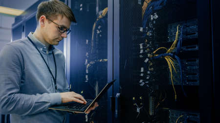 In Data Center IT Engineer Stands Before Working Server Rack Doing Routine Maintenance Check and Diagnostics Using Laptop. Visible Computer Hardware Equipment, Broadband Fiber Optic Cables LED Lights. Banque d'images
