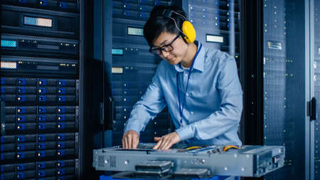 In the Modern Data Center: IT Engineer Wearing Protective Muffs Installs New Hardware for Server Rack. IT Specialist Doing Maintenance, Updating Hardware for Stable Functioning of Database System. Zdjęcie Seryjne