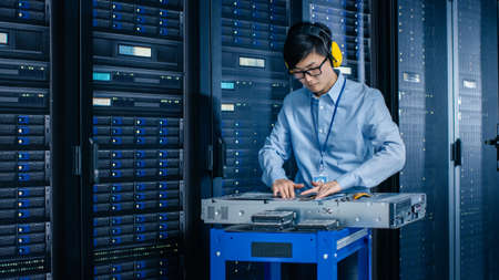 In the Modern Data Center: IT Engineer Wearing Protective Muffs Installs New Hardware for Server Rack. IT Specialist Doing Maintenance, Updating Hardware for Stable Functioning of Database System.