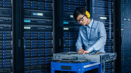 In Data Center: IT Engineer Wearing Protective Muffs Installs New Hardware for Server Rack. Specialist Doing Maintenance, Running Diagnostics and Updating Hardware for Stable Functioning of a System.