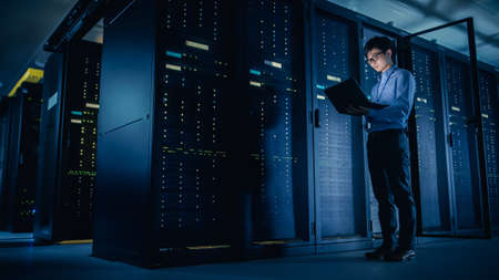 In Data Center: Male IT Technician Running Maintenance Programme on a Laptop, Controls Operational Server Rack Optimal Functioning. Modern High-Tech Telecommunications Operational Super Computer.