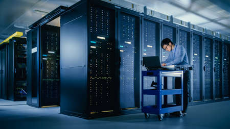 In the Modern Data Center: IT Engineer Doing Maintenance and Diagnostics. Pushes Cart alongside Server Racks, Ready to Install New Hardware for Planned System Update, Equipment Replacement.