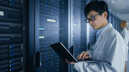In Data Center: Male and Female IT Specialists Wearing White Coats Work with Server Racks, Use Laptops to Run Maintenance Diagnostics. People wearing Lab Coats Working with Datacenter Database. Archivio Fotografico