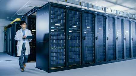 In Data Center: Male IT Specialist Wearing White Coat Walks Alongside Row of Server Racks, Uses Laptop Computer to Run Maintenance Diagnostics Tools, Controls so that Database Works Smoothly.