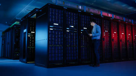 In Data Center: Male IT Specialist Walks along the Row of Operational Server Racks, Uses Laptop for Maintenance. Concept for Telecommunications, Cloud Computing, Artificial Intelligence, Supercomputer Banque d'images
