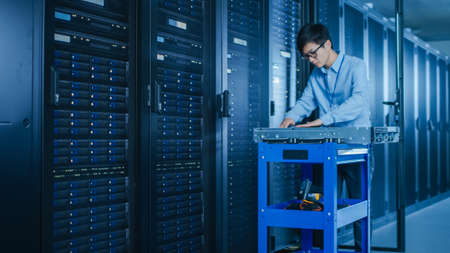 In the Modern Data Center: IT Technician Working with Server Racks, on a Pushcart Various Equipment Needed for Installing New Hard Drives, Doing Hardware Maintenance and Diagnostics. Foto de archivo