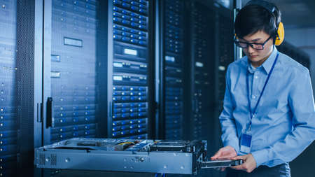 In the Modern Data Center: IT Technician Working with Server Racks, on a Pushcart Installing New Hardware. Engineer Doing Maintenance and Diagnostics of the Database. 写真素材