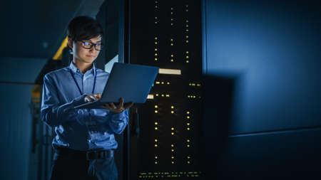 In Dark Data Center: Male IT Specialist Stands Beside the Row of Operational Server Racks, Uses Laptop for Maintenance. Concept for Cloud Computing, Artificial Intelligence, Supercomputer