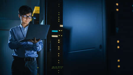 In Dark Data Center: Male IT Specialist Stands Beside the Row of Operational Server Racks, Uses Laptop for Maintenance. Concept for Cloud Computing, Artificial Intelligence, Supercomputer Archivio Fotografico