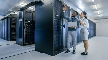 Black IT Technician with a Laptop Computer Gives a Tour to a Young Intern. They Talk in Data Center while Walking Next to Server Racks. Running Diagnostics or Doing Maintenance Work.