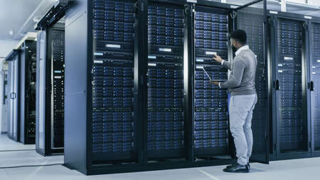 Black IT Specialist is Working on Laptop in Data Center while Standing Before Server Rack. Running Diagnostics, Putting in Data or Doing Maintenance Work.