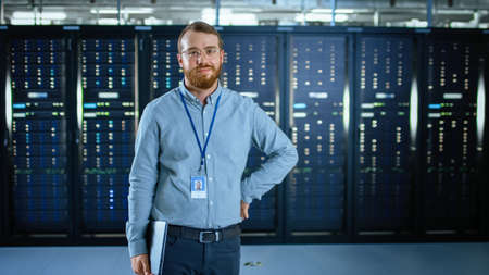 Bearded IT Specialist in Glasses is Standing in Data Center Next to Server Racks, Smiling to the Camera and Holding Laptop. Running Diagnostics or Doing Maintenance Work.