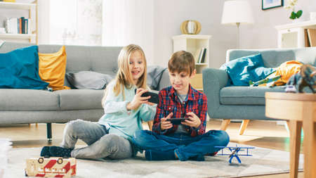 At Home Sitting on a Carpet: Cute Little Girl and Sweet Boy Playing in Competitive Video Game on two Smartphones, Holding them in Horizontal Landscape Mode. Girl Wins and Celebrates.