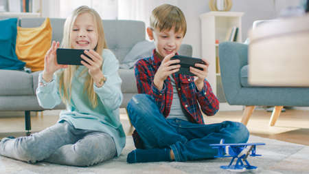 At Home Sitting on a Carpet: Cute Little Girl and Sweet Boy Playing in Competitive Video Game on two Smartphones, Holding them in Horizontal Landscape Mode.