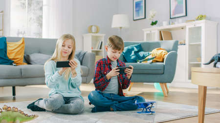 At Home Sitting on a Carpet: Cute Little Girl and Sweet Boy Playing in Competitive Video Game on two Smartphones, Holding them in Horizontal Landscape Mode. Stock Photo