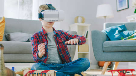 Smart Little Boy Wearing Virtual Reality Headset Uses Hand Gestures to Control Augmented Reality Gameplay. Hes Sitting on a Carpet in His Living Room. Happy Child Uses Futuristic AR Glasses at Home.