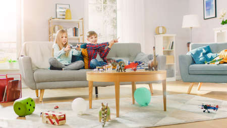 At Home: Cute Girl Playing in Video Game Console, Using Joystick Controller, Her Younger Brothe Cheers for Her. Happy Children Playing Videogames.