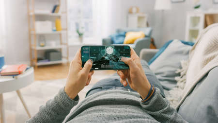 Man at Home Lying on a Couch using Smartphone, Holds it Horizontally in Landscape Mode. He is Playing First Person Shooter Video Game. Point of View Camera Shot.