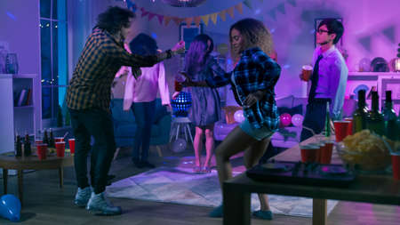 At the College House Party: Diverse Group of Friends Have Fun, Dancing and Socializing. Boys and Girls Dance in the Circle. Disco Neon Strobe Lights Illuminating Room. Reklamní fotografie