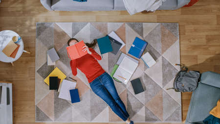 Young Girl in Red Coat and Blue Jeans is Lying Down on a Floor, Reading a Notebook. Looks Above, Smiles and Laughs. Cozy Living Room with Modern Interior with Carpet, Workbooks and Backpack. Top View.