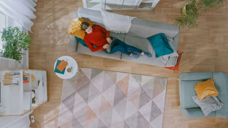 Young Girl in Red Blouse and Blue Jeans is Lying Down on a Sofa, Using a Laptop. She Looks Above and Smiles. Cozy Living Room with Modern Interior with Plants, Coffee Table and Wooden Floor. Top View.