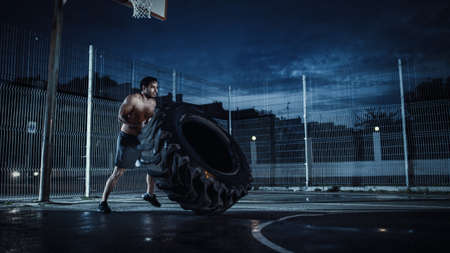 Strong Muscular Fit Young Shirtless Man is Doing Exercises in a Fenced Outdoor Basketball Court. Hes Flipping a Big Heavy Tire at Night After Rain in a Residential Neighborhood Area. Stock fotó