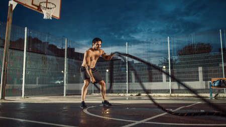 Strong Muscular Fit Shirtless Young Man is Doing Exercises with Battle Ropes. He is Doing a Workout in a Fenced Outdoor Basketball Court. Evening After Rain in a Residential Neighborhood Area.