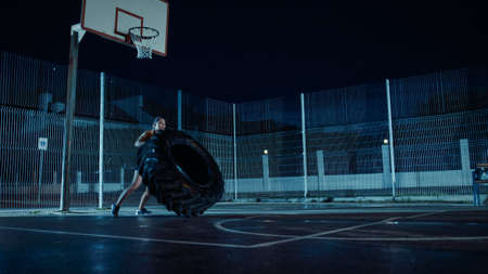 Beautiful Energetic Fitness Girl is Doing Exercises in a Fenced Outdoor Basketball Court. Shes Flipping a Big Heavy Tire in a Foggy Night After Rain in a Residential Neighborhood Area.