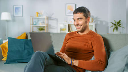 Handsome Man Uses Laptop Computer while Sitting on Sofa at Home. Man Working, Browsing Through Internet from His Cozy Living Room.