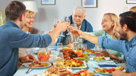 Big Family and Friends Celebration at Home, Diverse Group of Children, Young Adults and Old People Gathered at the Table have Fun Conversation. Clinking Glasses and Making Toast. Archivio Fotografico