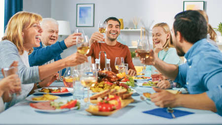 Big Family and Friends Celebration at Home, Diverse Group of Children, Young Adults and Old People Gathered at the Table have Fun Conversation. Clinking Glasses and Making Toast.