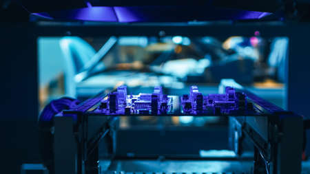 Automated Robotic Industrial Equipment is Testing Electronic Printed Circuit Board with Purpule Neon Light and Laser Technology After Assembly. Stockfoto