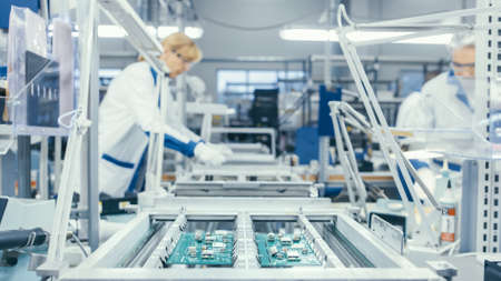 Shot of an Electronics Factory Workers Assembling Circuit Boards by Hand While it Stands on the Assembly Line. High Tech Factory Facility. Banque d'images