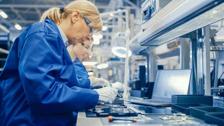Female Electronics Factory Worker in Blue Work Coat and Protective Glasses is Assembling Smartphones with Screwdriver. High Tech Factory Facility with more Employees in the Background.