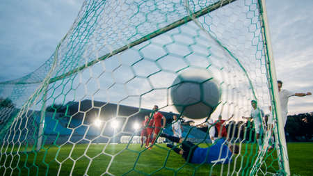 On Soccer Championship Goalkeeper Tries to Defend Goals but Jumps and Fails to Catch the Ball. Shot from Behind the Net with the Ball in it. Whole Stadium Visible.