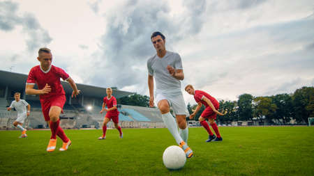 Professional Soccer Player Leads with a Ball, Masterfully Dribbling and Bypassing Sliding Tackles of His Opponents. Two Professional Football Teams Playing. Low Angle Shot. Standard-Bild