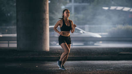Shot of a Beautiful Fitness Girl in Black Athletic Top and Shorts Jogging in a Dark Foggy Street. She is Running in an Urban Environment Under a Bridge with Cars in the Background.