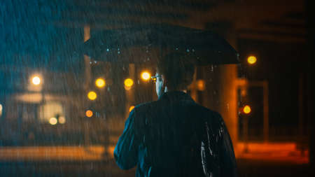 Backshot of a Young Caucasian Shorthaired Man, Wearing a Jeans Coat Walking in the Rain Under an Umbrella. Hes Walking at Night in the City. Imagens