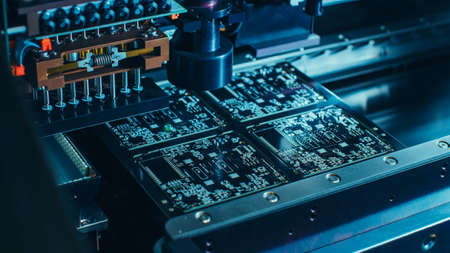 Macro Close-up Shot of Printed Circuit Board on a Factory Assembly Line with Automated Robotic Arm for Surface Mounting Microprocessors to the Motherboard.