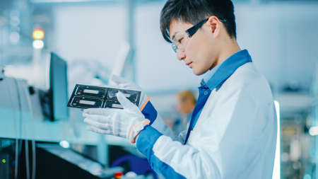 High-Tech Factory: Quality Control Engineer Checks Electronic Printed Circuit Board it for Damages. In the Background Assembly Line for PCB with Surface Mount Pick and Place Technology.