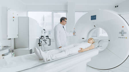 In Medical Laboratory Radiologist Controls MRI or CT or PET Scan with Female Patient Undergoing Procedure. Professional Doctor Conducts Emergency Checkup Procedure with Advanced Medical Technologies. Foto de archivo