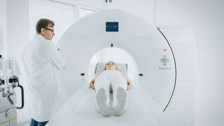 In Medical Laboratory Male Radiologist Controls MRI or CT or PET Scan with Female Patient Undergoing Procedure. Doctor Conducts Emergency Scanning with Advanced Medical Technologies. Foto de archivo